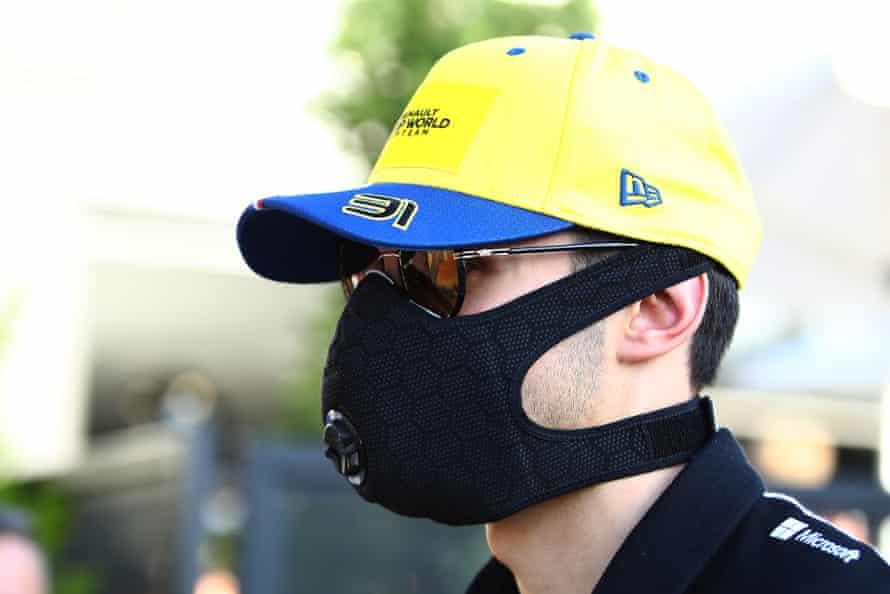 Renault's Esteban Ocon walks through the paddock wearing a mask.