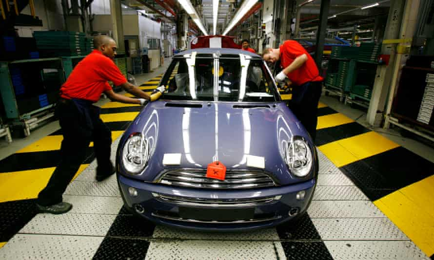 Workers put the finishing touches to a car on BMW's Mini production line at Cowley, Oxford.