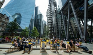 People sit on deckchairs near the Lloyds of London building during the heatwave.