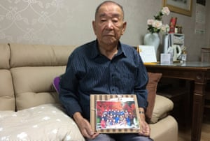 Kim Myeong-do holds his only family photograph.