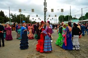 Women wear the traditional trajes de flamenca, or flamenco dresses
