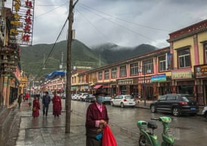 People walk the street near the Labrang Monastery in Xiahe, an ethnically-Tibetan town in Gansu province, China