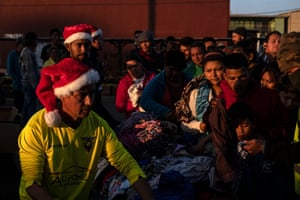 Central American migrants traveling to the United States, line up to receive gifts from a NGO (Non-governmental organization) as part of the Christmas celebrations outside a temporary shelter downtown Tijuana, Baja California state, Mexico on December 24, 2018.