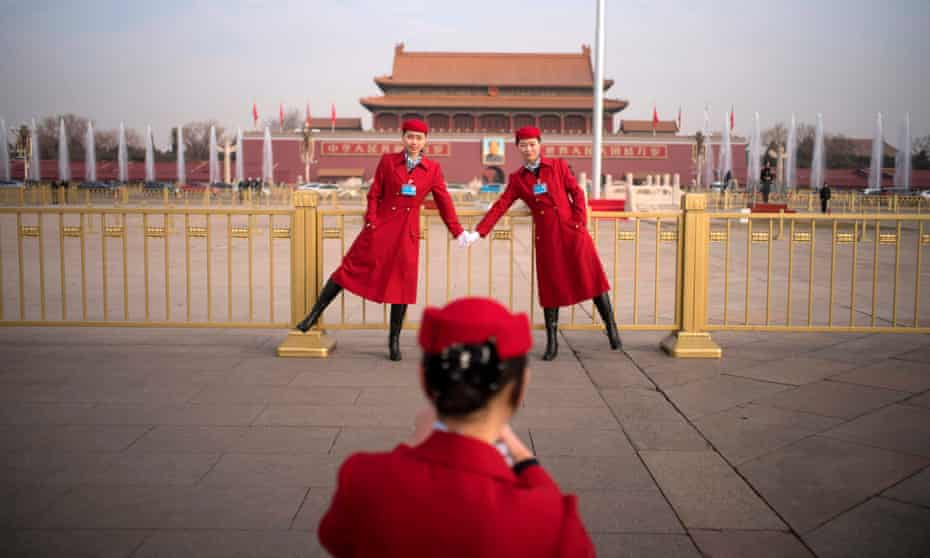 Chinese hostesses pose at Tiananmen square during the opening session of the National People's Congress in Beijing on Monday
