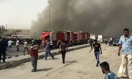 Iraqi security forces and civilians gather at the scene of a deadly suicide car bomb attack in New Baghdad, Iraq.