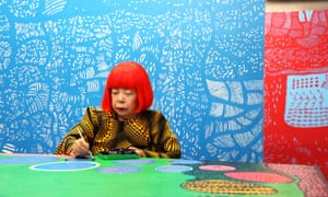 Yayoi Kusama at work in her studio, in front of her painting The Moving Moment When I Went to the Universe.