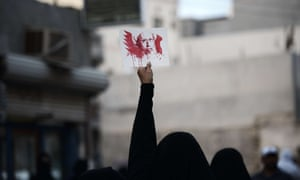 A Bahraini woman holds a placard bearing a portrait of Nimr during a protest in Jidhafs, west of Manama