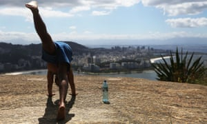 A man performs yoga at the top of the Babilônia favela.