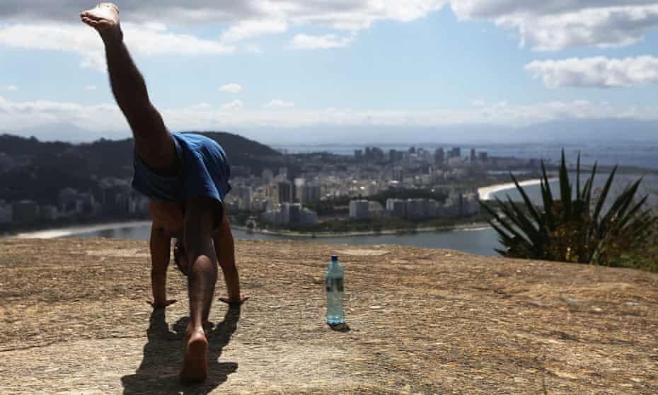 A man performs yoga at the top of the Babilônia favela.