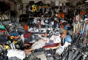 An Afghan man rests in his shop as he sell US secondhand goods outside the base.