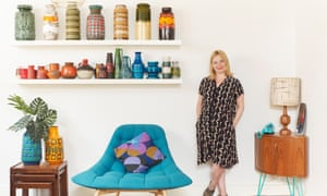 Ellie Howitt in her sitting room standing next to a teal chair and with shelving holding large ceramic pots above