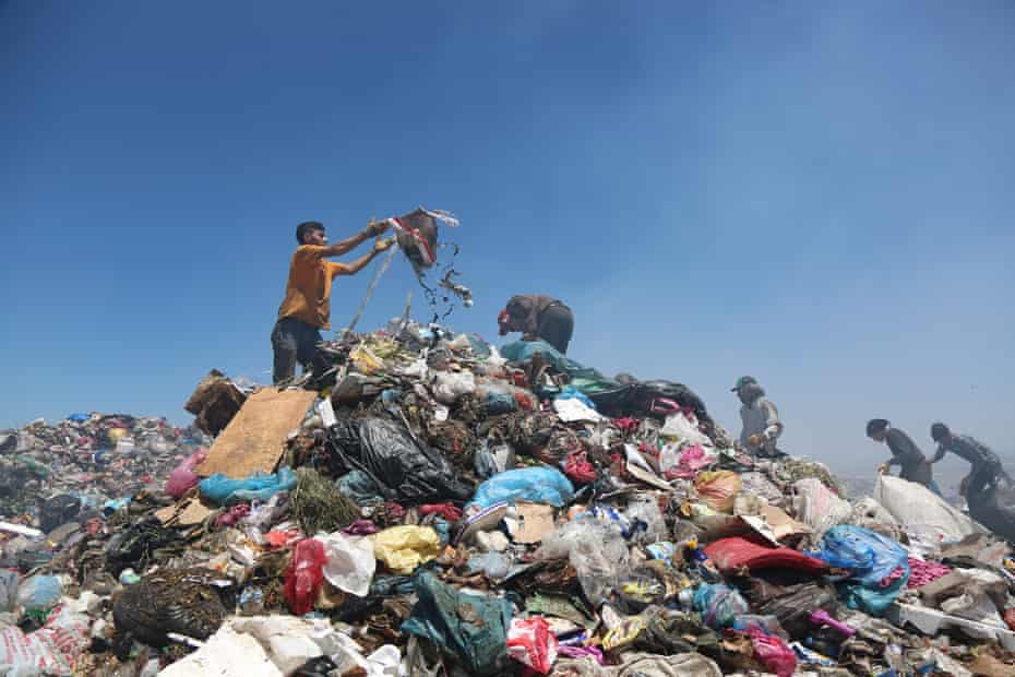 Men search through pieces suitable for recycling at the municipal garbage dump in the south-eastern city of Diyarbakir, Turkey.