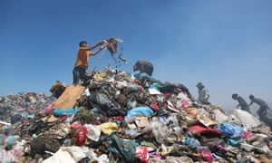 Men search through pieces suitable for recycling at the municipal garbage dump in Diyarbakir, Turkey.