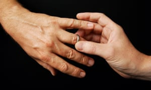 A man places a ring on another man's finger