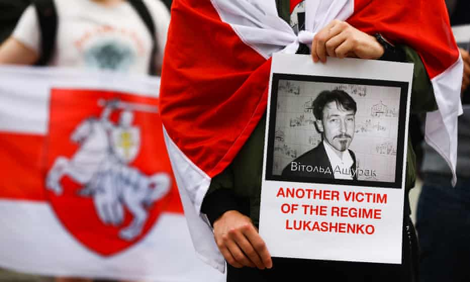 A protester holds a picture of Vitold Ashurak in Kraków, Poland, after the activist's death in a Belarus prison