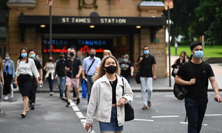 Commuters wearing face masks exit St James Station in the CBD in Sydney on Monday. From Monday, people not wearing masks inside public spaces, including shopping centres and public transport in Sydney can be fined up to $200. NSW is on high alert over an expected surge in Covid cases linked to the BWS liquor store in Berala.