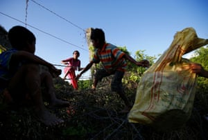 Children pass their belongings over the border fence as they try to enter Bangladesh in Bandarban