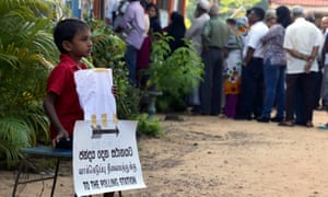 A boy waits for his parents to return from voting as he sits behind a sign showing the way to the polling station (bottom) and to the toilets (top) as voters line up to vote in the presidential elections, at Kelaniya in Colombo, Sri Lanka.