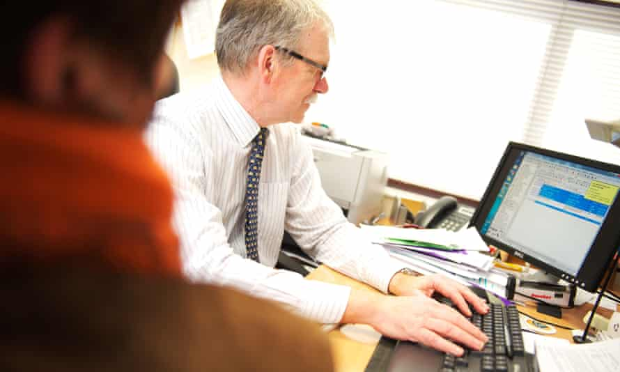 A GP looks up medical records while with a patient