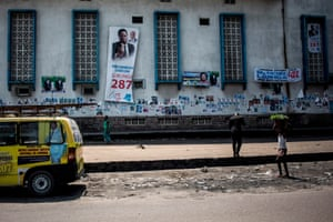 A girl carries vegetables past a building plastered with campaign posters in Lingwala