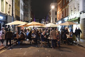 People dine out in London's Soho neighbourhood before 10pm.