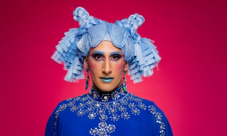 Amrou Al-Kadhi in drag, with bright blue hair in plaits and tied up, on a pink/red background