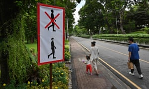 A couple and their child walk past a sign advising visitors to wear face masks at Lumpini Park in Bangkok.