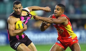 Josh Gibson of the Hawks is tackled by Gold Coast's Touk Miller