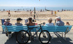 People watch a game of beach volleyball on Boscombe beach in Dorset.
