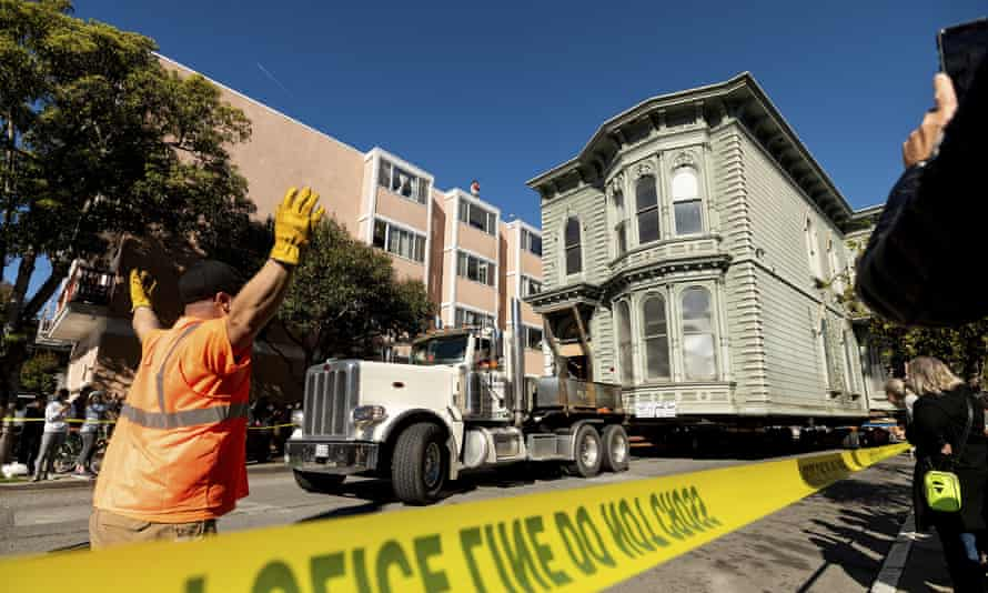 A worker signals to a truck driver pulling a Victorian home through San Francisco on Sunday.