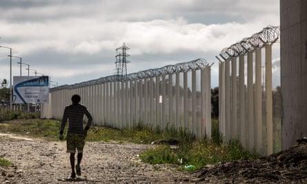 A migrant walks along a perimeter fence in Calais, France