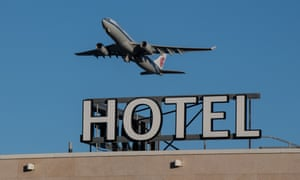 An airplane passes over a Sofitel hotel as it takes off from a runway at Heathrow Airport