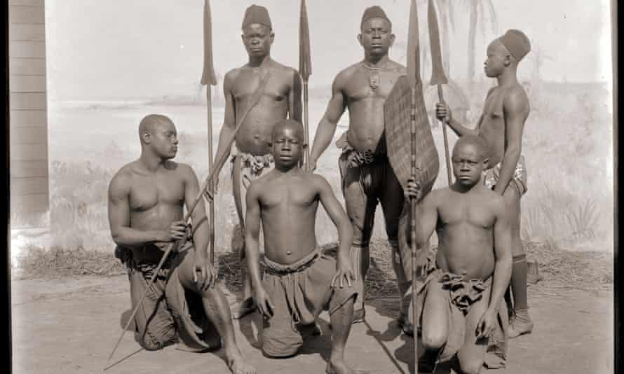 Congolese men pose in front of a painted backdrop for the world fair in Antwerp in 1894.