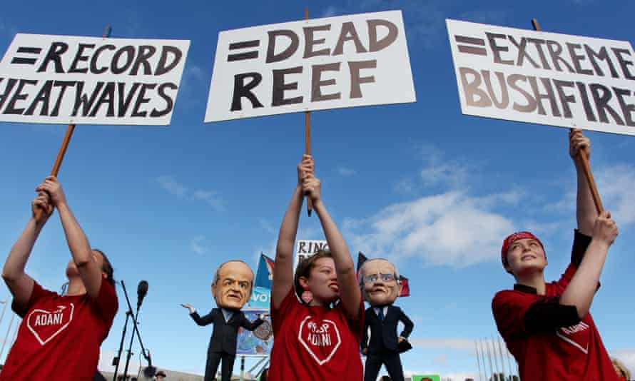 Young environmental activists hold protest signs up in front of comedians dressed as Labor leader Bill Shorten and prime minister Scott Morrison in Canberra.