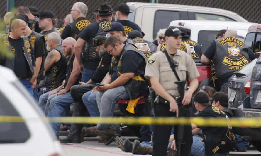 A McLennan county deputy stands guard near a group of bikers in the parking lot of a Twin Peaks restaurant in Waco, Texas.