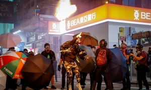 A pro-democracy protester throws a fire bottle towards riot police during a rally against police brutality in Hong Kong, China, 27 October 2019