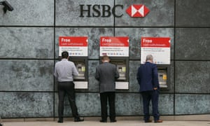 People withdraw money from a cash machine at a HSBC branch in London.