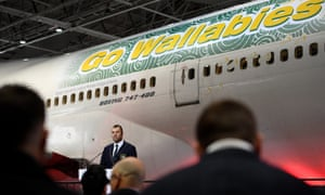Michael Cheika, the Australia coach, in front of a plane emblazoned with the words Go Wallabies