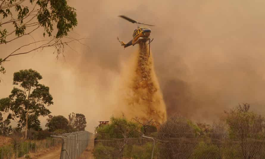 A helicopter drops retardant as WA firefighters work to contain a fire outside Wooroloo
