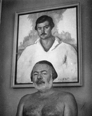 A photograph of Hemingway at the Finca Vigia in Cuba in 1952, posing in front of Waldo Peirce's 1929 oil portrait, Kid Balzac, which depicts him
