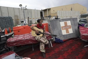 An Afghan soldier plays a guitar that was left behind