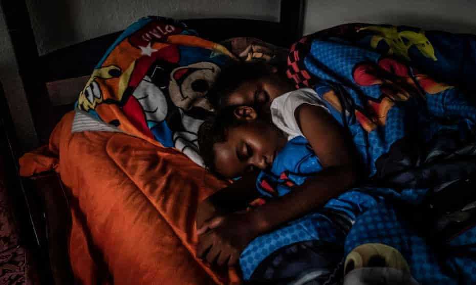 Cherokeena Robinson, 32, lays in bed with her son Mai'Kel Stephens, 6, at their transitional house in San Pedro, California.