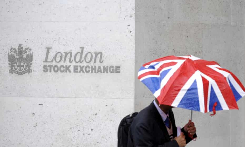 A man sheltering under a Union Jack umbrella walking along a wall bearing the logo of the London Stock Exchange