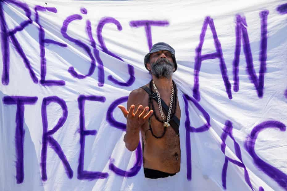 A man emerges through a banner saying 'resist and trespass' at the 'kill the bill' protest