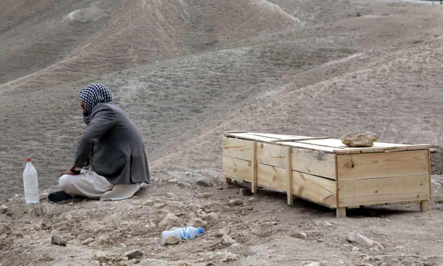 A man sits beside the coffin of his relative who was killed in a suicide bomb attack in Kabul, Afghanistan.