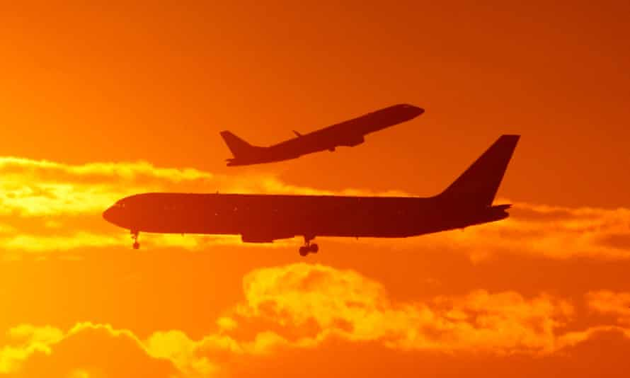 Planes fly against an orange cloudy sky