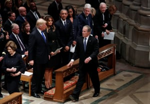 George W Bush walks past his fellow former presidents and his successor Donald Trump as he arrives at the state funeral for his father.