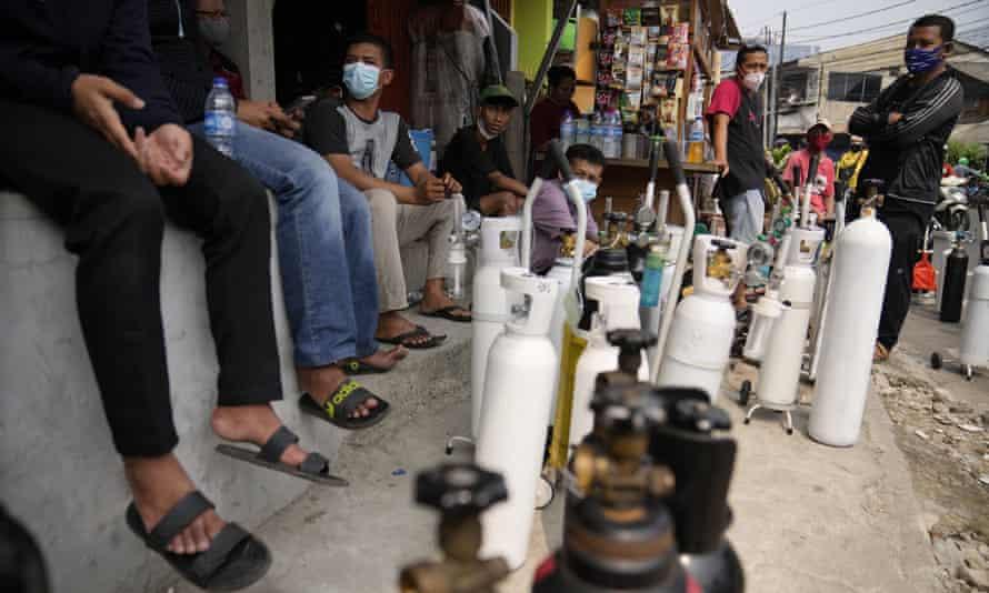 Orangorang mengantri untuk mengisi tabung oksigen mereka di Jakarta