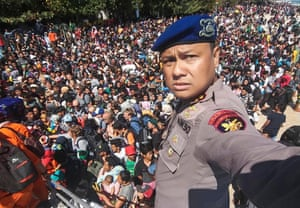 Chief of the Marine Police of Lombok, Dewa Wijaya (front) takes a picture in front of hundreds of local and foreign tourists gathering on the beach after the earthquake.
