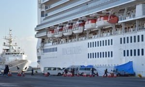 Ambulances wait for patients who tested positive for the new coronavirus onboard the Diamond Princess cruise ship in Yokohama, Japan, on Thursday.